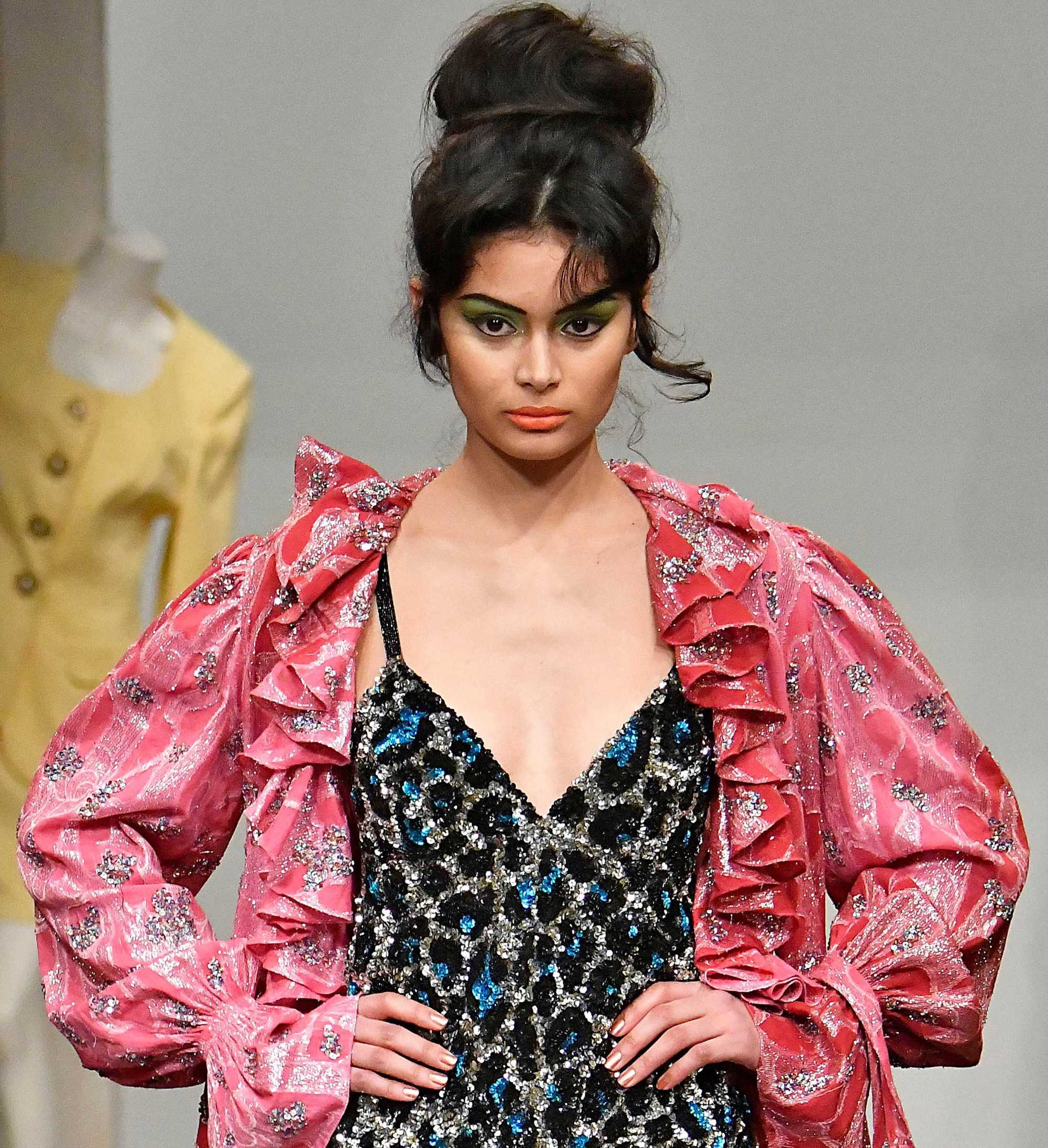 easy vintage hairstyles: close up shot of model on the ashish runway with 60s style volumised bun updo, wearing pink dressing grown and sparkly slip dress