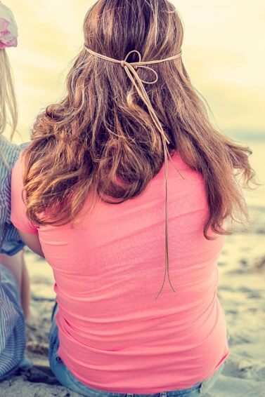 beach hair products to pack: two girls sitting on the beach, one with blonde long hair and one with brunette long hair