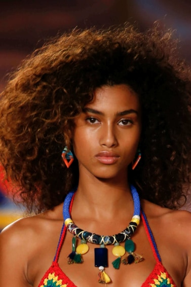 model with a big curly afro on the runway wearing tribal style clothing and jewellery