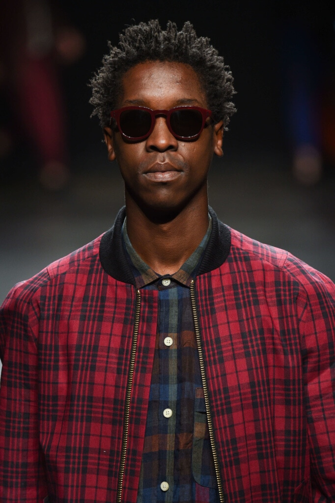 close up shot of man with mini twisted afro, wearing red jacket and checked top on the runway