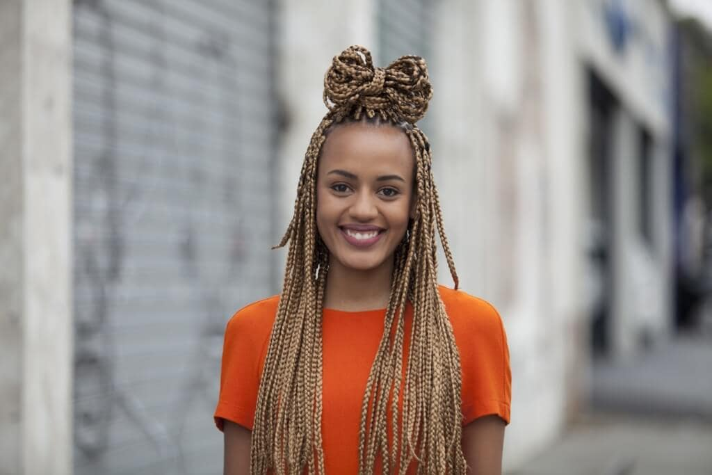 Cute box braids: Young black woman with half-up, half-down bow bun