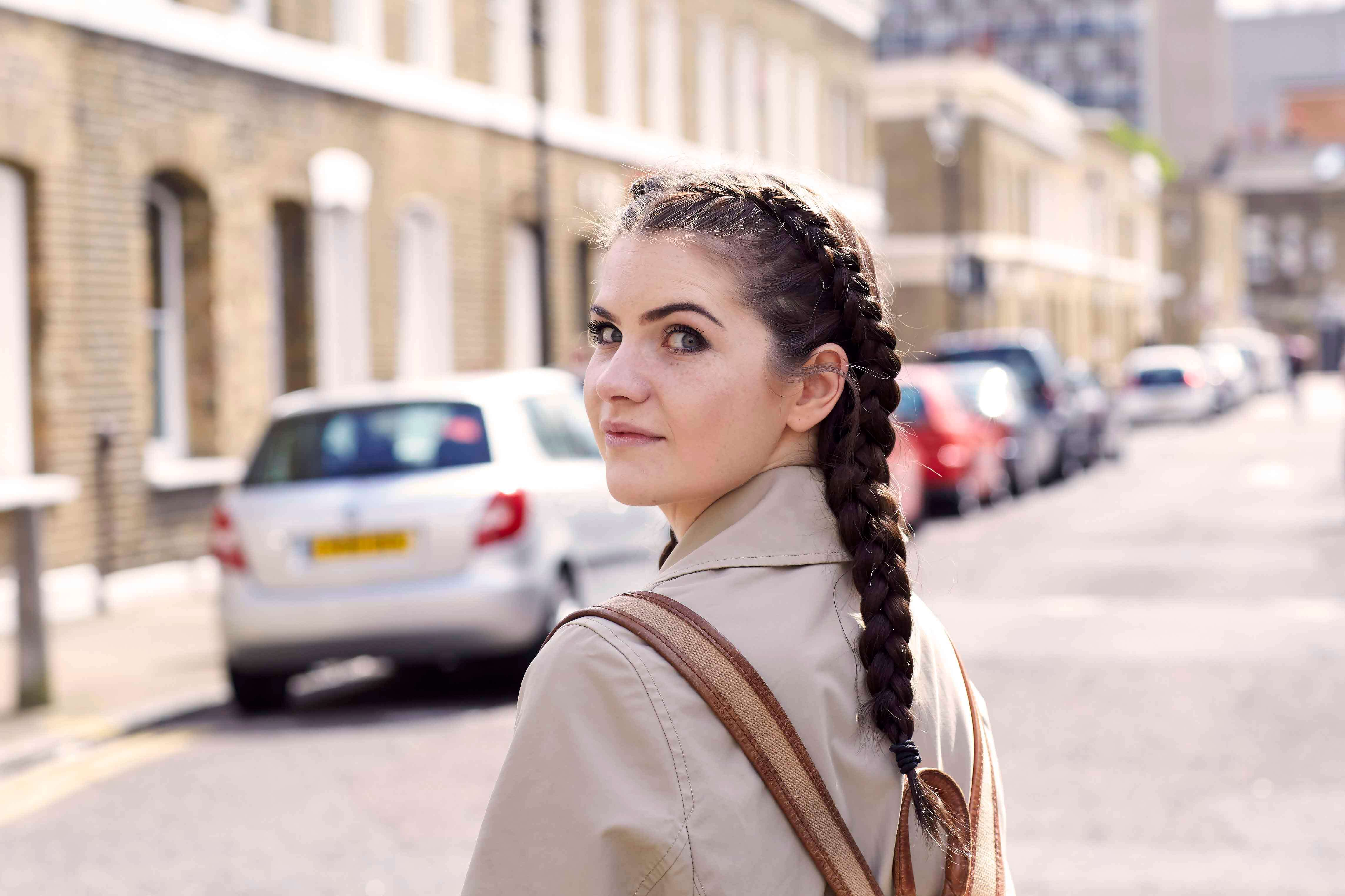 Best hairspray: Woman with brown long hair in double boxer braids wearing a backpack and beige jacket.