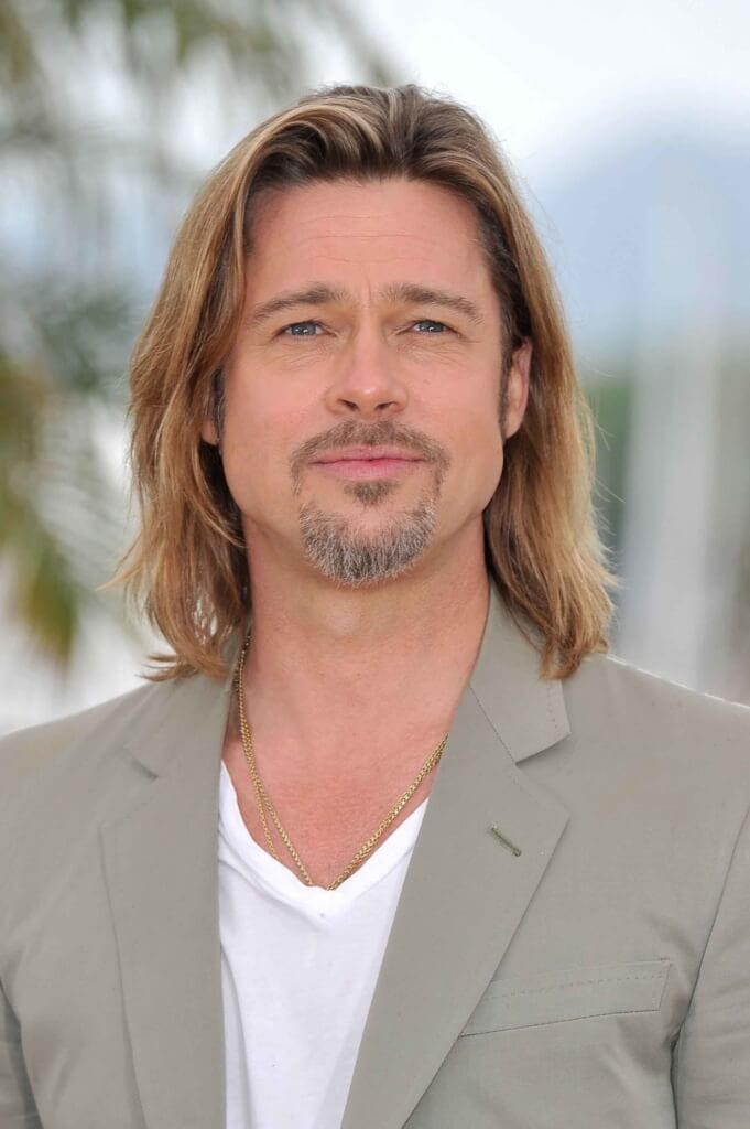 brad pitt with shoulder length blonde hair wearing a grey suit jacket and a white t-shirt