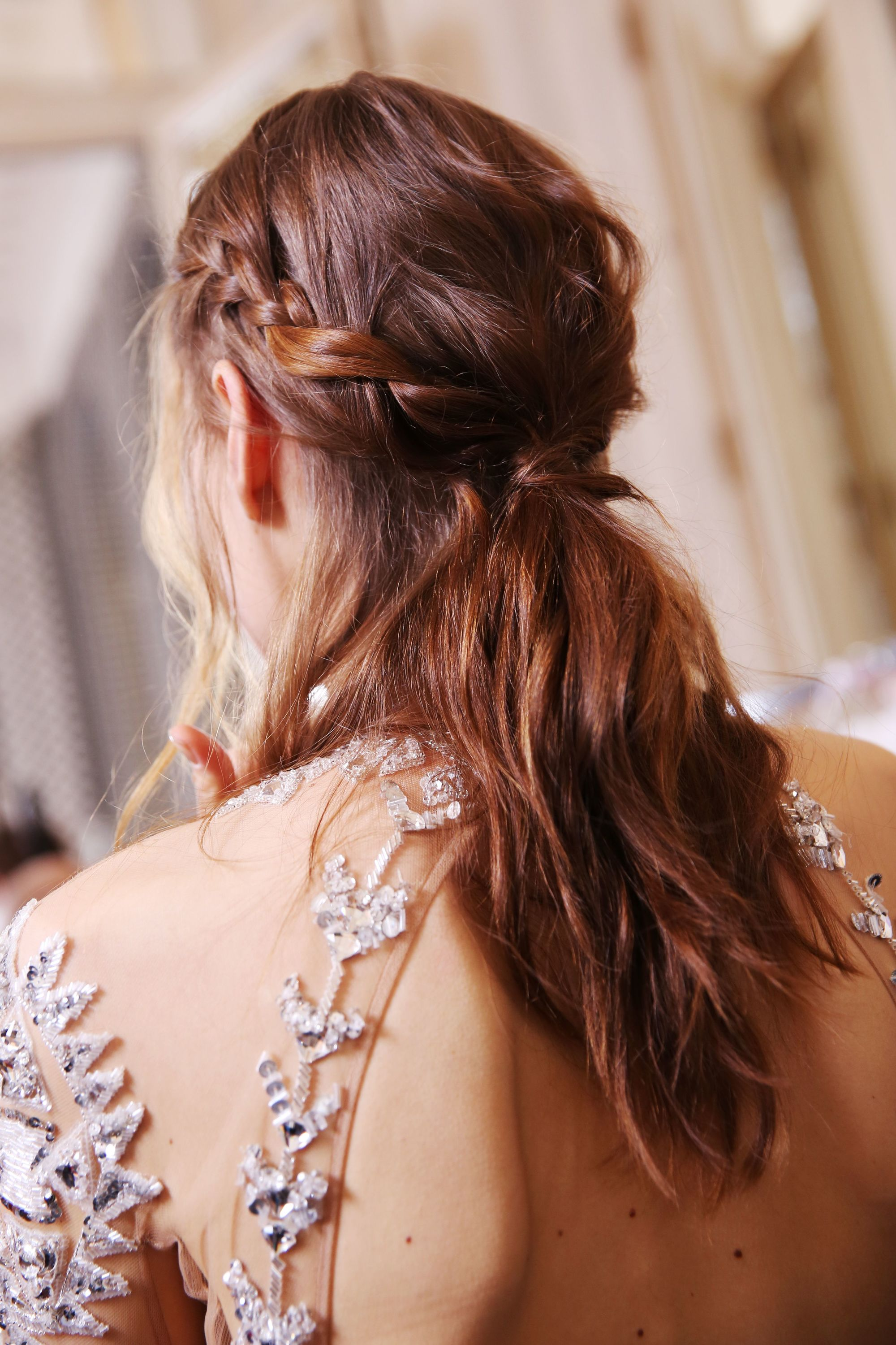 brunette model backstage wearing an embroidered sheer dress with her hair in a braided half up half down