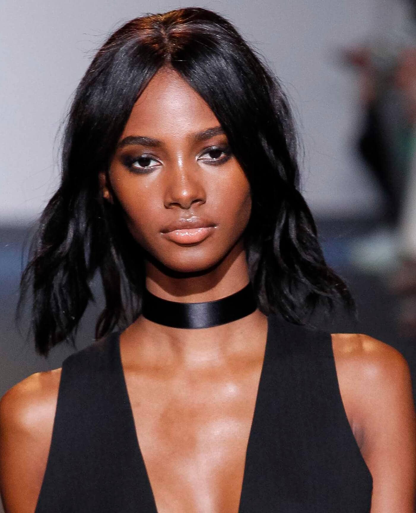 Hair straightening treatment: Model with relaxed dark brown shoulder length hair wearing a black vest and choker on runway.