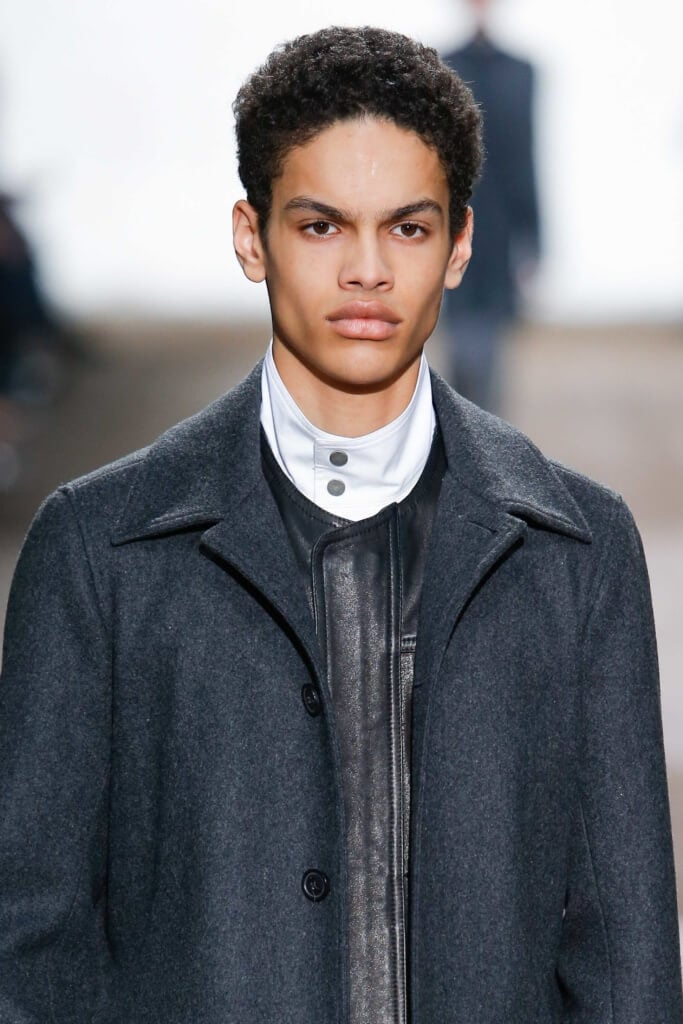close up shot of a male model with mini afro hairstyle, wearing jacket on the runway