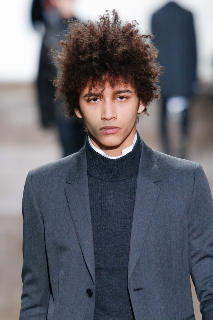 close up shot of male model on runway with tapered afro hairstyle, wearing smart outfit