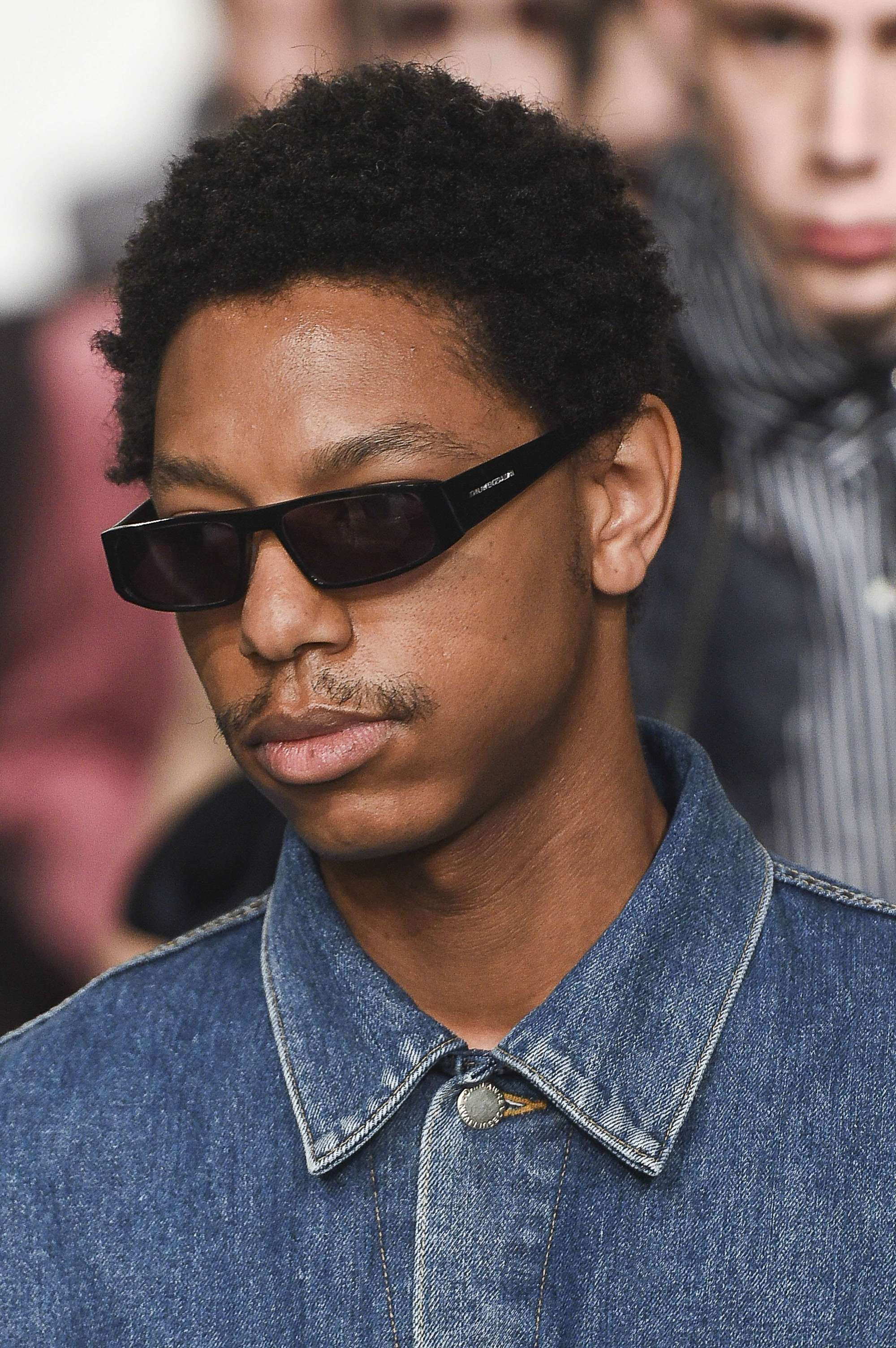 close up shot of black man with a short afro hairstyle, wearing glasses and denim shirt