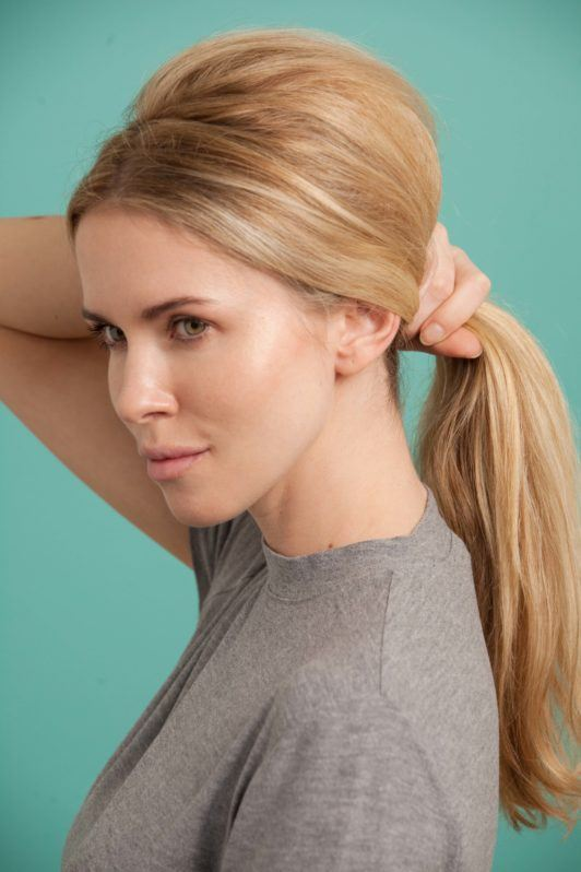a blonde woman pulling back her hair