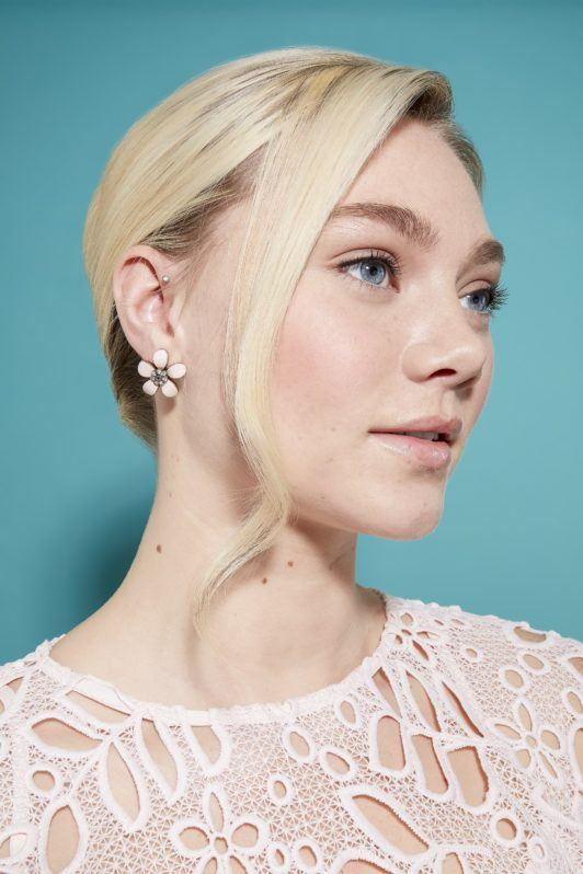 model with light blonde hair rolled into a french twist updo, with loose hair at the front of her look to frame here face
