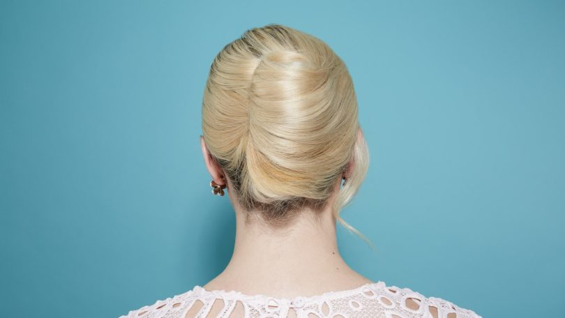 back view of a model with light blonde hair rolled into a french twist updo