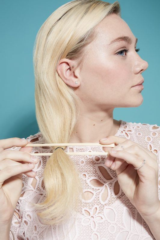 model with light blonde hair and darker roots using chopsticks hold her hair ready to roll it into a an updo