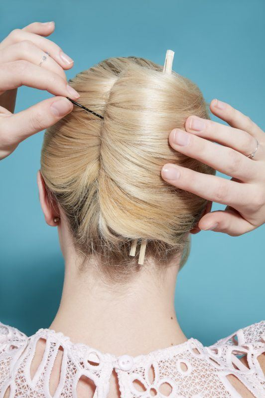 model with light blonde hair rolled into a french twist updo, pinning it in place with a bobby pin