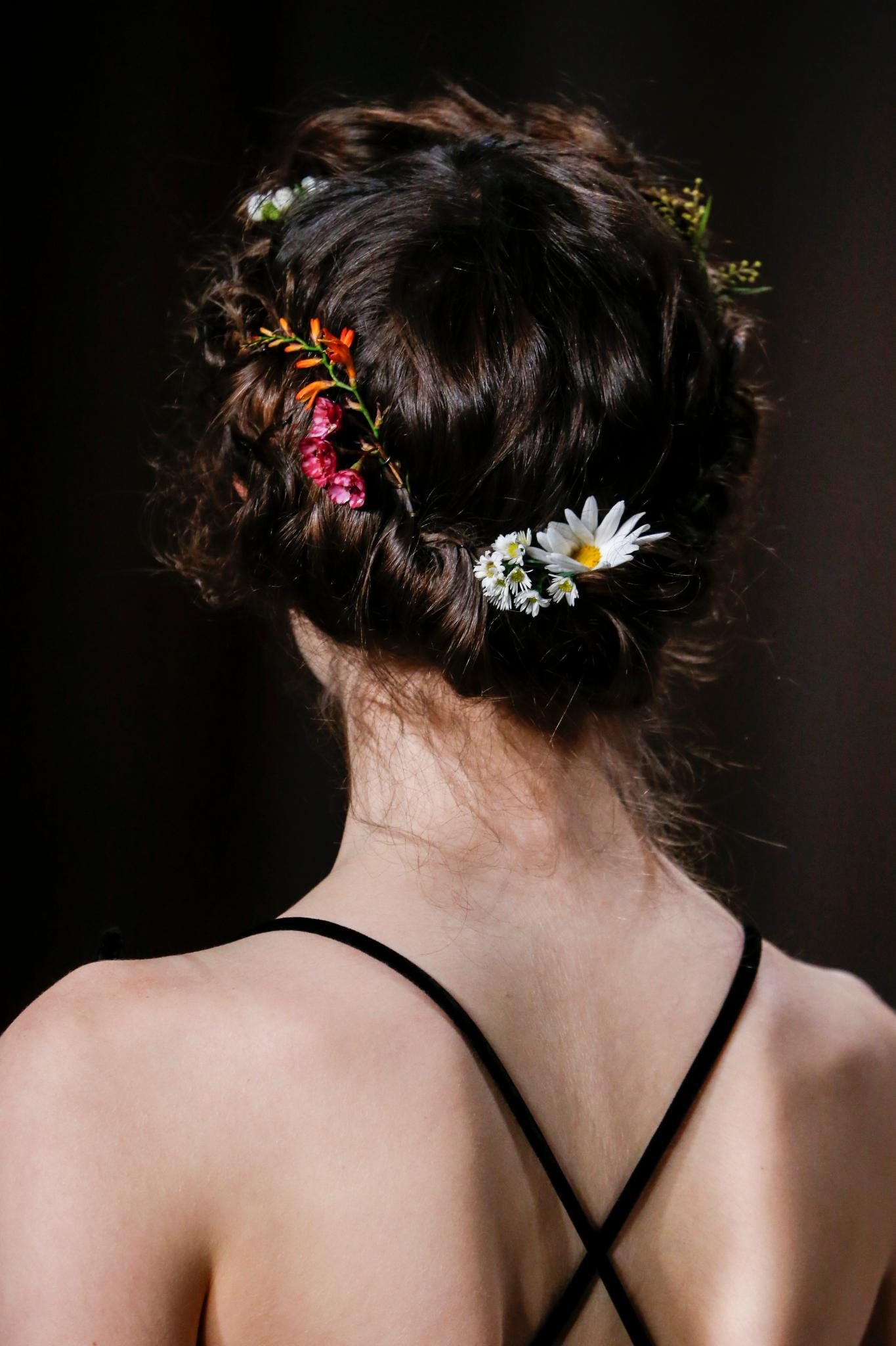 easy vintage hairstyles: close up shot of model on the valentino runway with Gibson tuck-inspired hair, with flowers in it, wearing all black