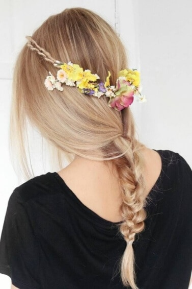 back view of a woman with long blonde hair styled into a loose braid and accessorised with a flower headband