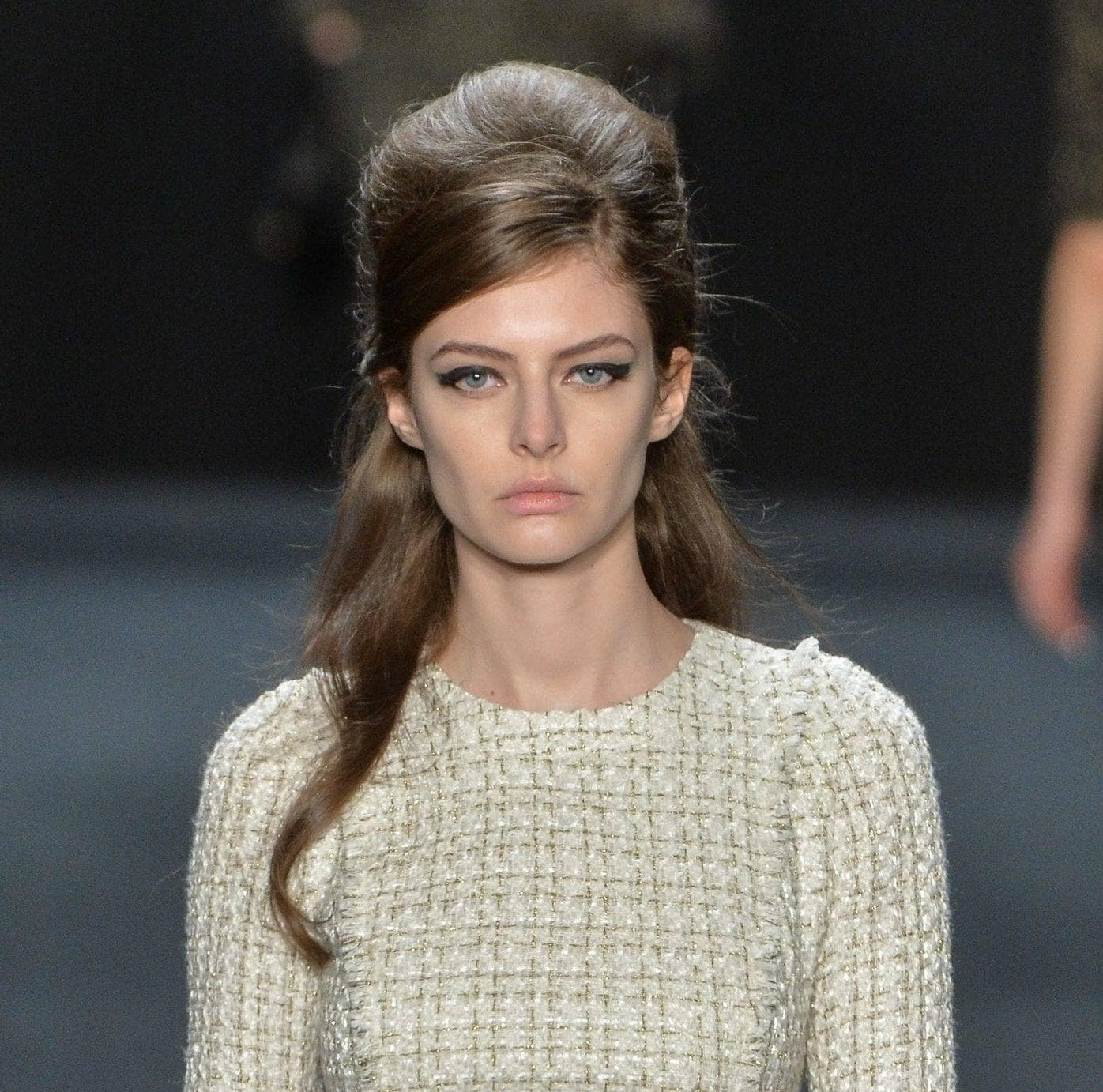 easy vintage hairstyles: close up shot of model on the runway with a half-up, half down bouffant hairstyle, wearing a checked dress