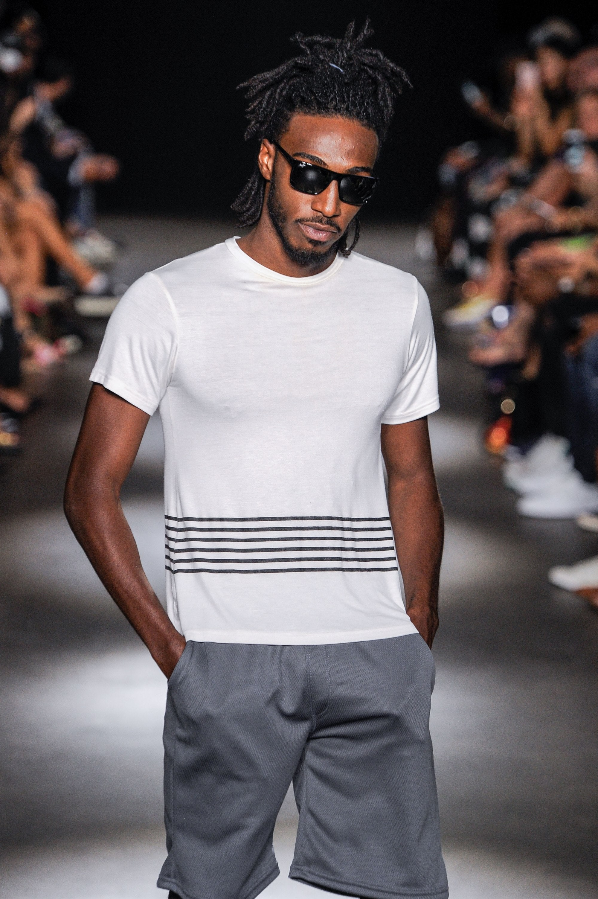 close up shot of black man with half up dreadlocks hairstyle, wearing white shirt and grey shirts on the grungy gentleman runway