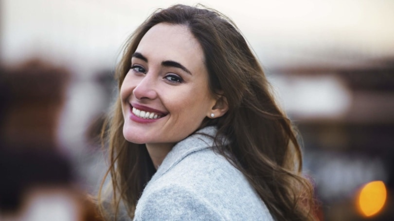 How to get healthy hair: Smiling brunette woman with long windswept hair