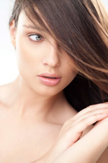 Dark brown haired woman touching her hair