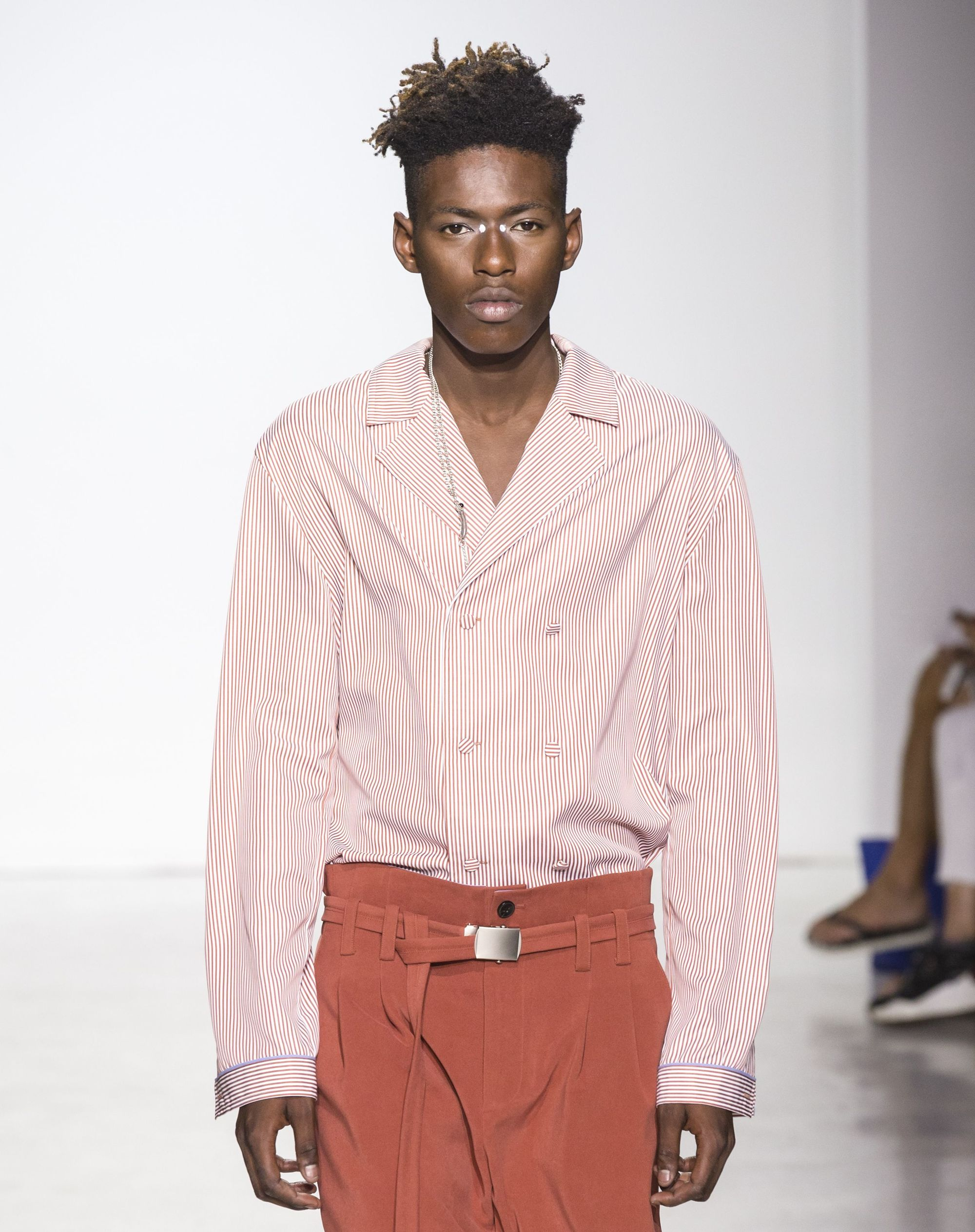 close up shot of black man with a high top skin fade hairstyle, wearing pink top and pink trousers on the general idea runway
