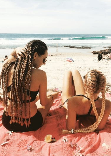 Summer hairstyles for long hair: two women with long cornrow hairstyles