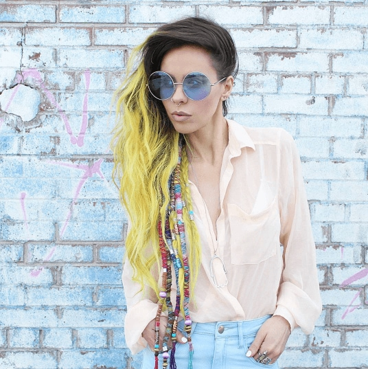 woman with long ombre yellow festival hair with hair wraps against a blue brick wall