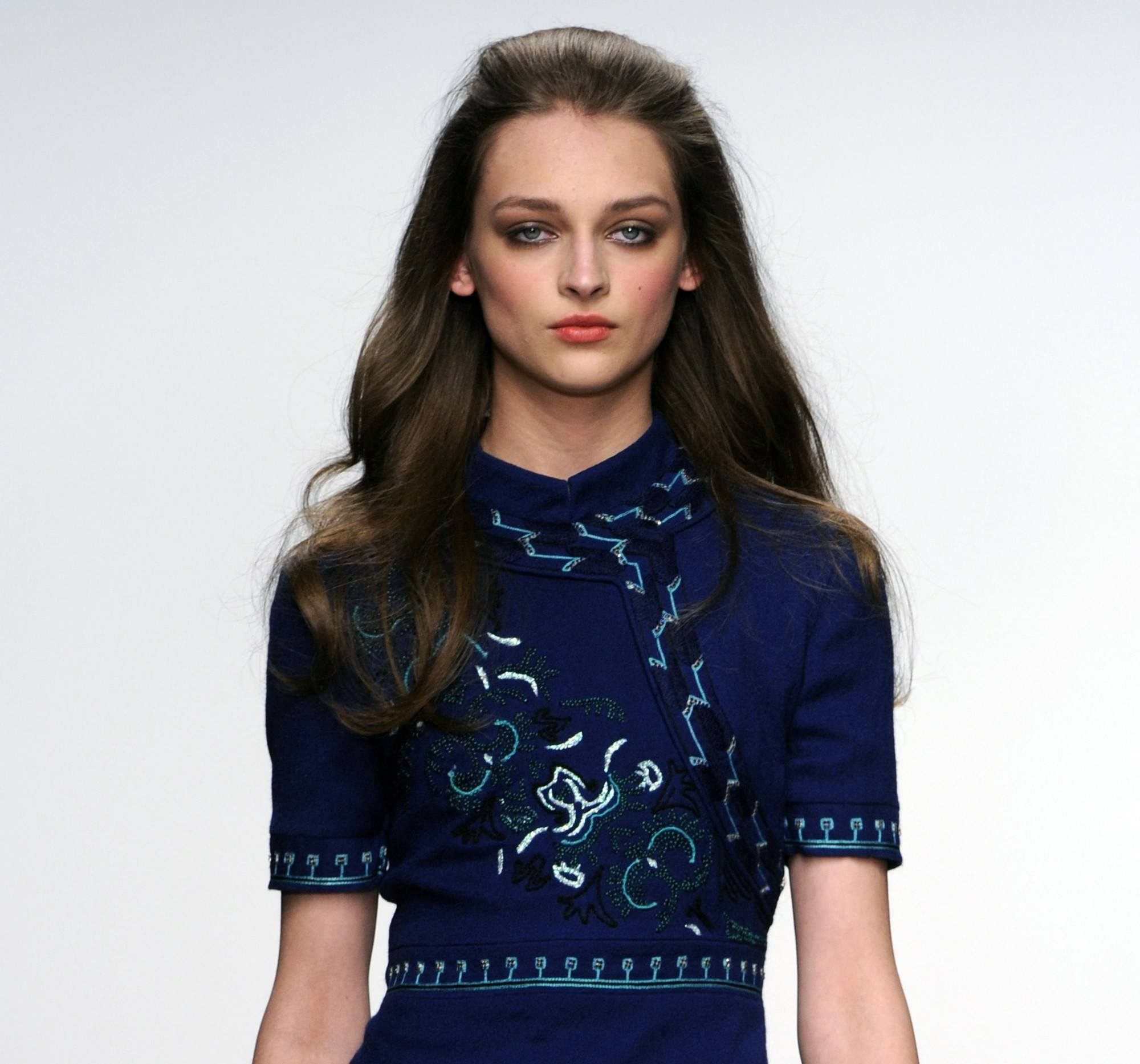 easy vintage hair ideas: close up shot of model on the Issa runway with Jackie O-inspired swept-back strands, wearing blue dress