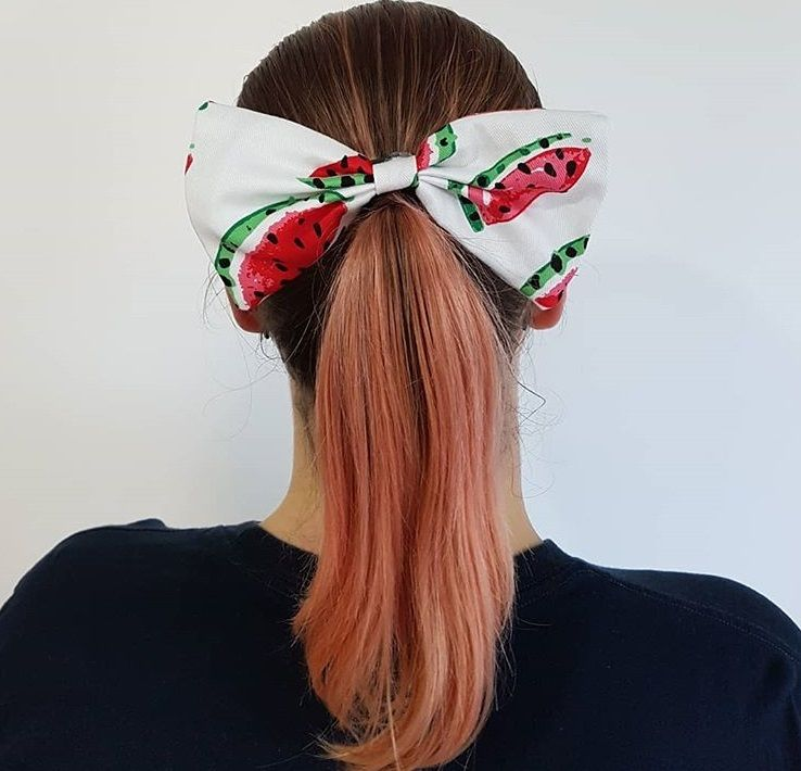 backshot of woman with a low ponytail that has a watermelon hair bow accessory on it