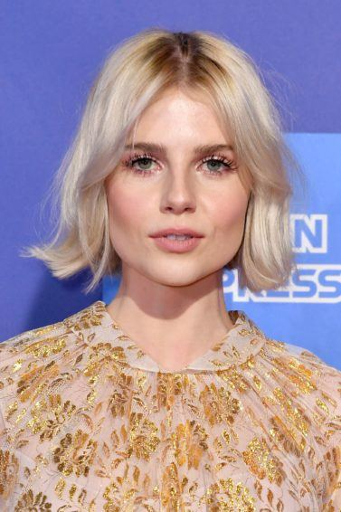 Hairstyles for thin hair: Lucy Boynton with her short platinum blonde hair styled into a short, flipped bob with Bardot bangs, wearing a floral top on the red carpet