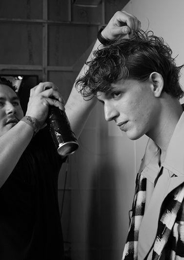 Kieron Webb styling a models tousled hair at Agi & Sam London Collections Men SS17 show