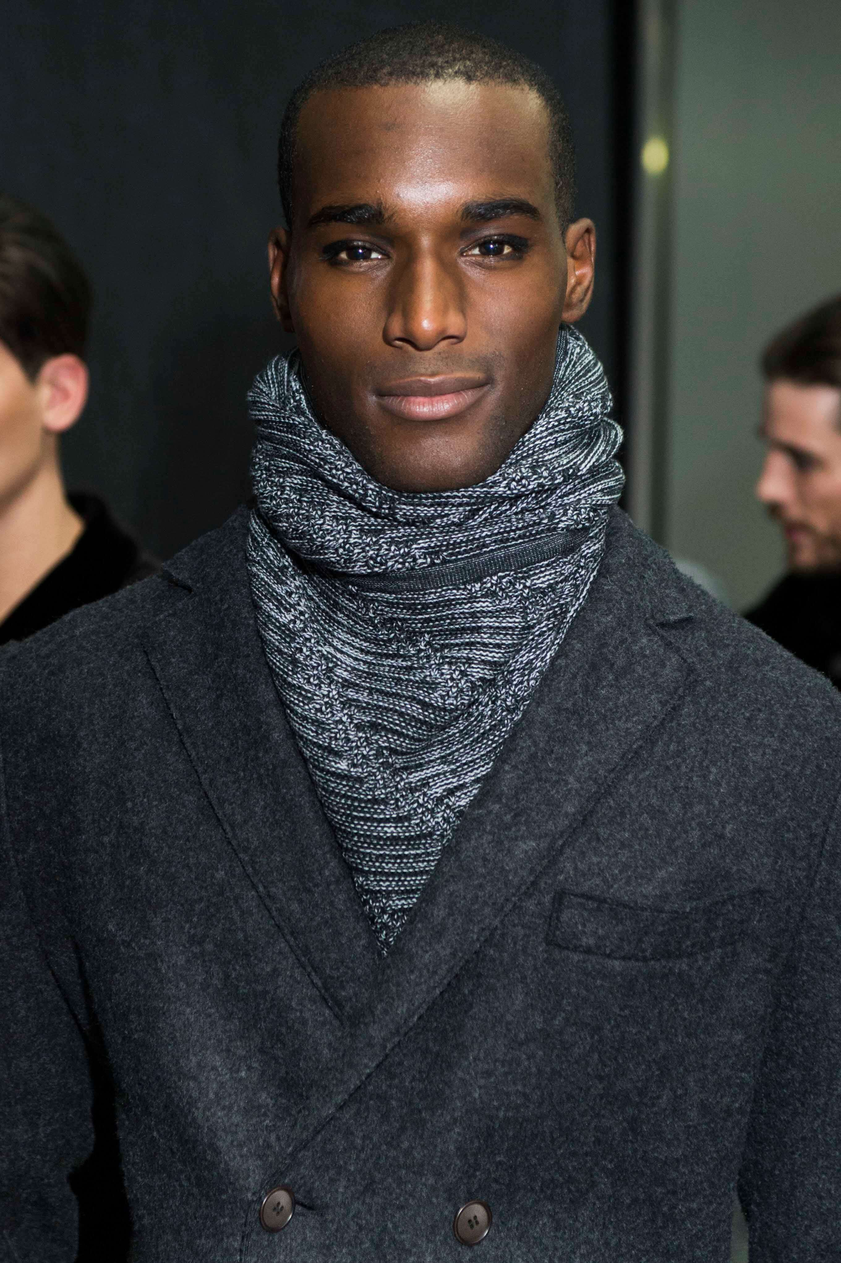 close up shot of a black male model with a buzz cut hairstyle, wearing jacket and scarf, backstage