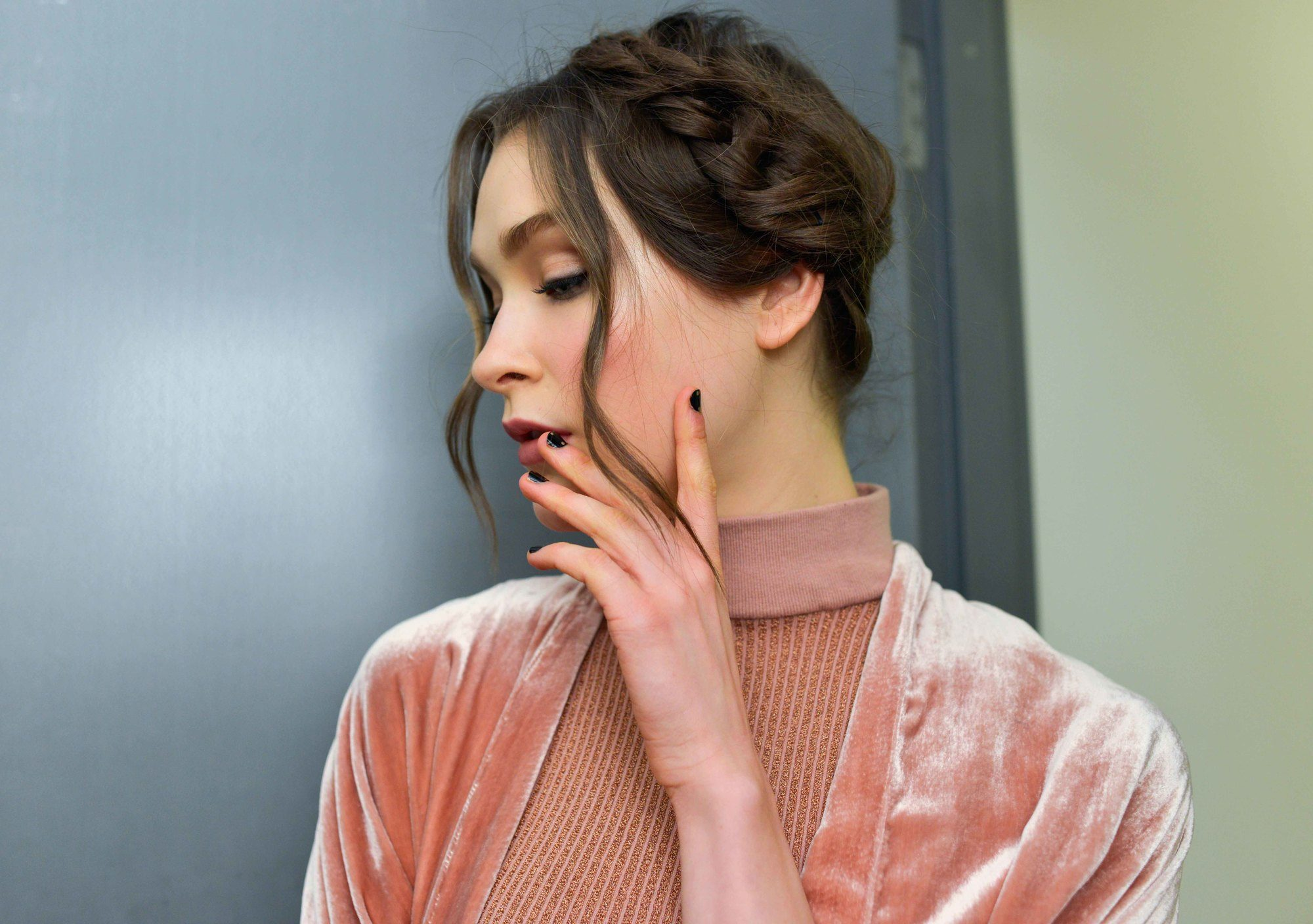brunette woman wearing a pink velvet high neck dress with her hair in a romantic milkmaid braid