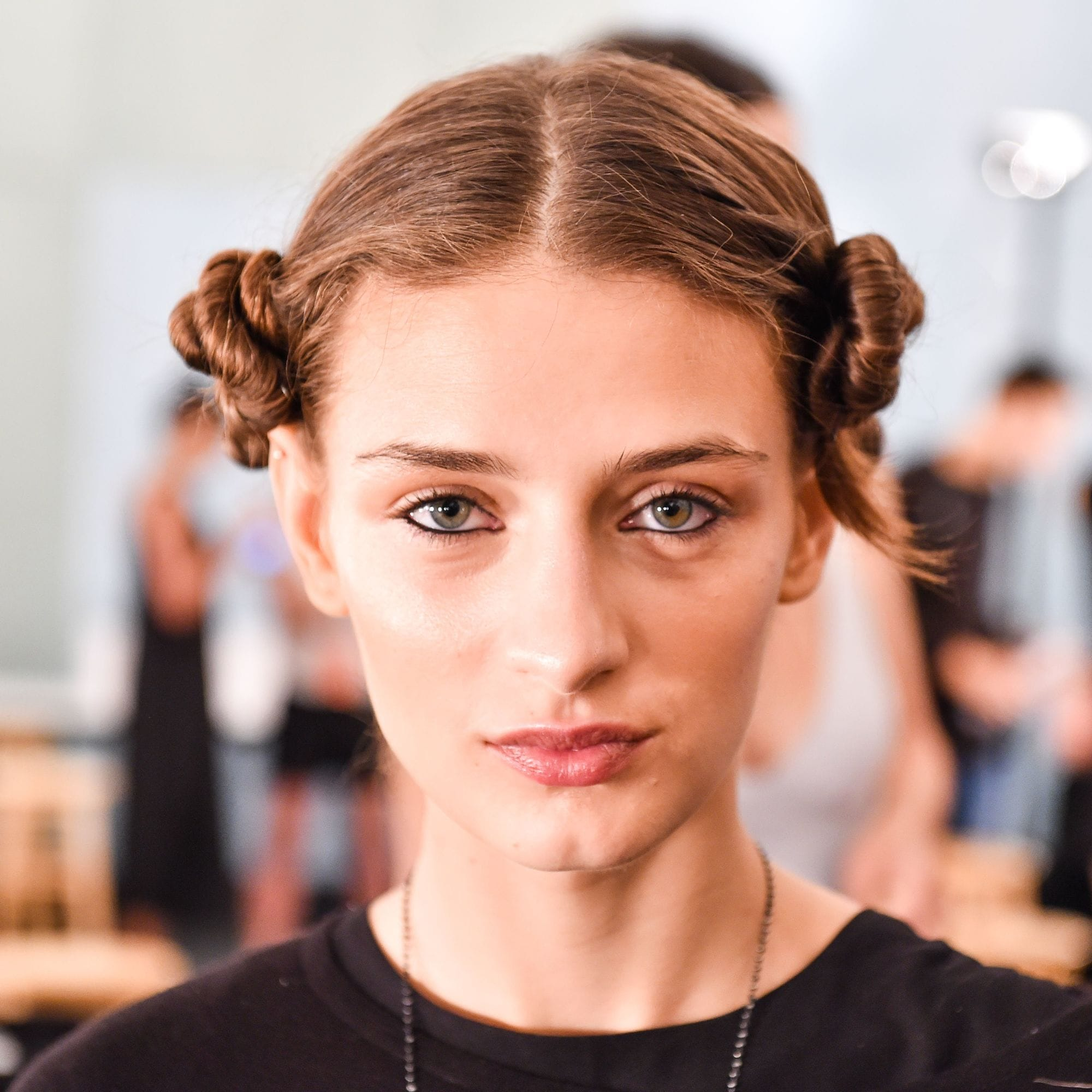 brunette model with her hair in mini buns