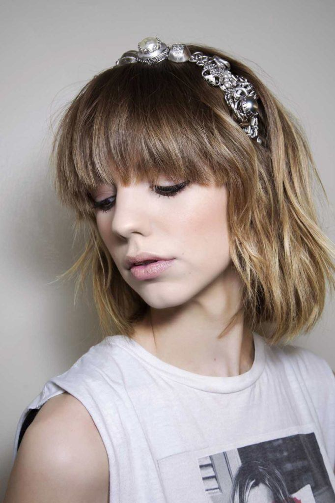 Blonde hair: Side view of a woman's face with a fringe and bobbed hair with a blonde ombre colour