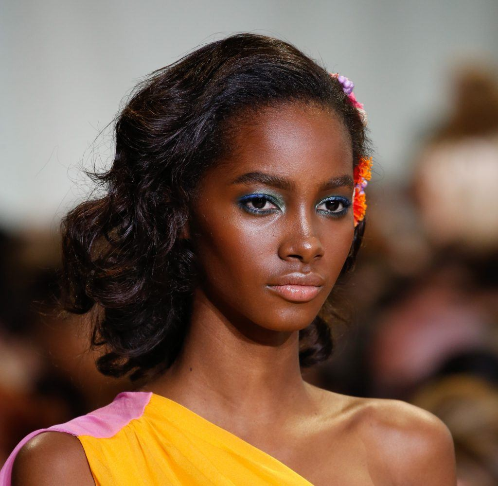 easy vintage hairstyles: close up shot of model on the diane von furstenberg runway with brushed out pin curls, with floral hair accessory, wearing yellow dress
