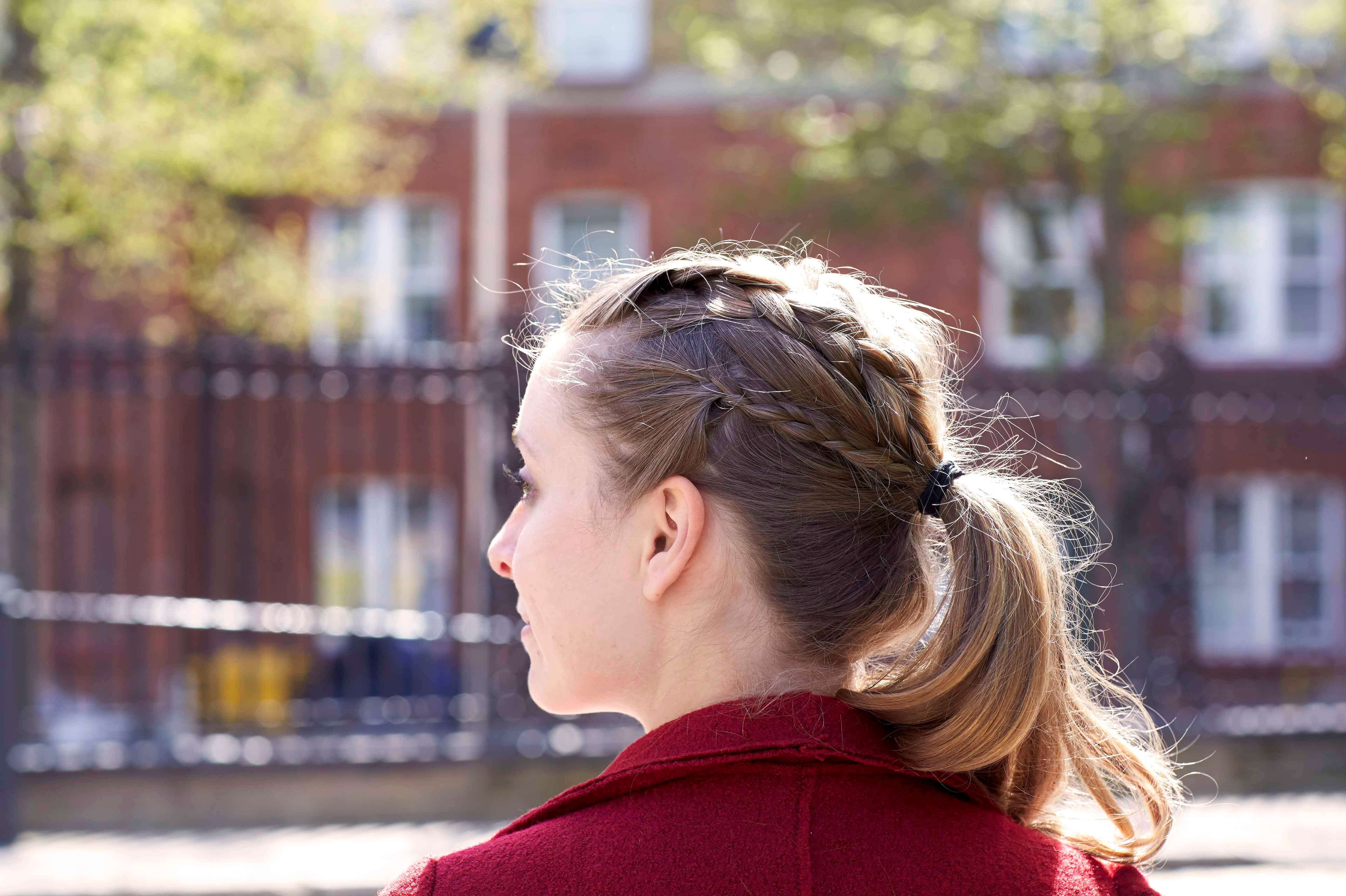 blonde girl with ponytail and plaits side view