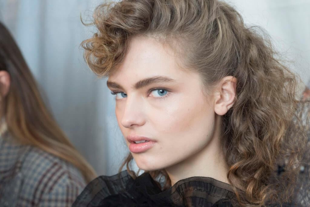 Model with curl retro-inspired, half-up half down curly quiff