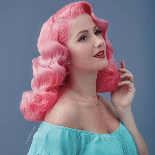 1940s hairstyles: image of a woman with pink hair in retro waves wearing a aqua blue top