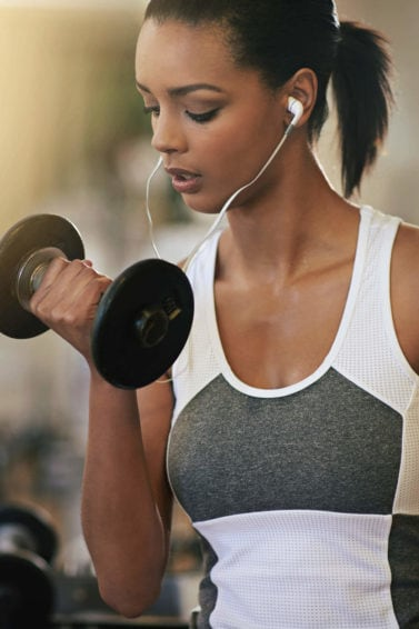 front view image of a woman in the gym lifting weights with her hair in a ponytail