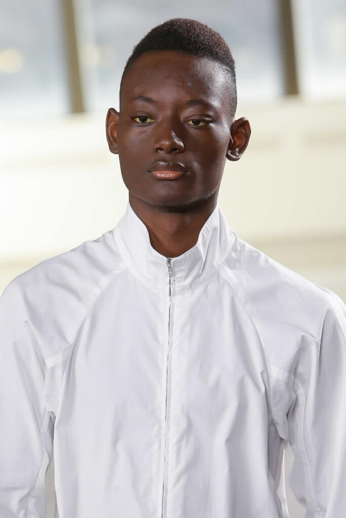close up shot of a black male model on the runway with south of france haircut, wearing white top