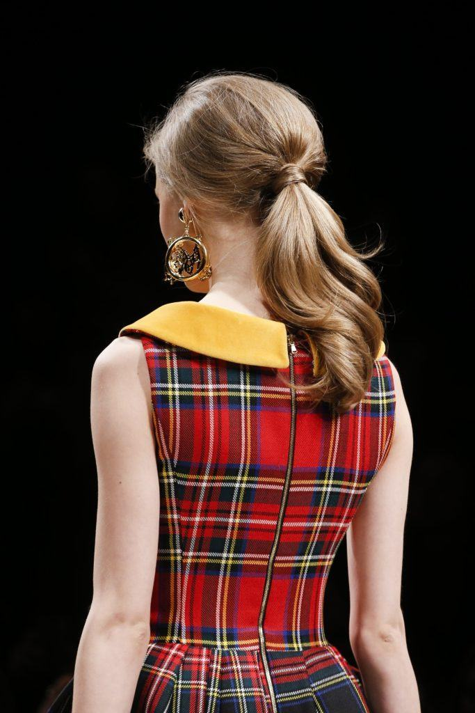 easy vintage hairstyles: close up shot of woman with low, teased ponytail, wearing plaid dress walking on the runway