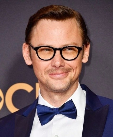 Jimmi Simpson wearing glasses and black tie and swept back hair