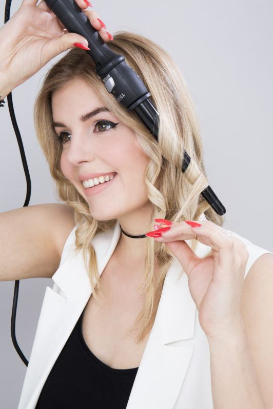 a blonde iron curling her hair