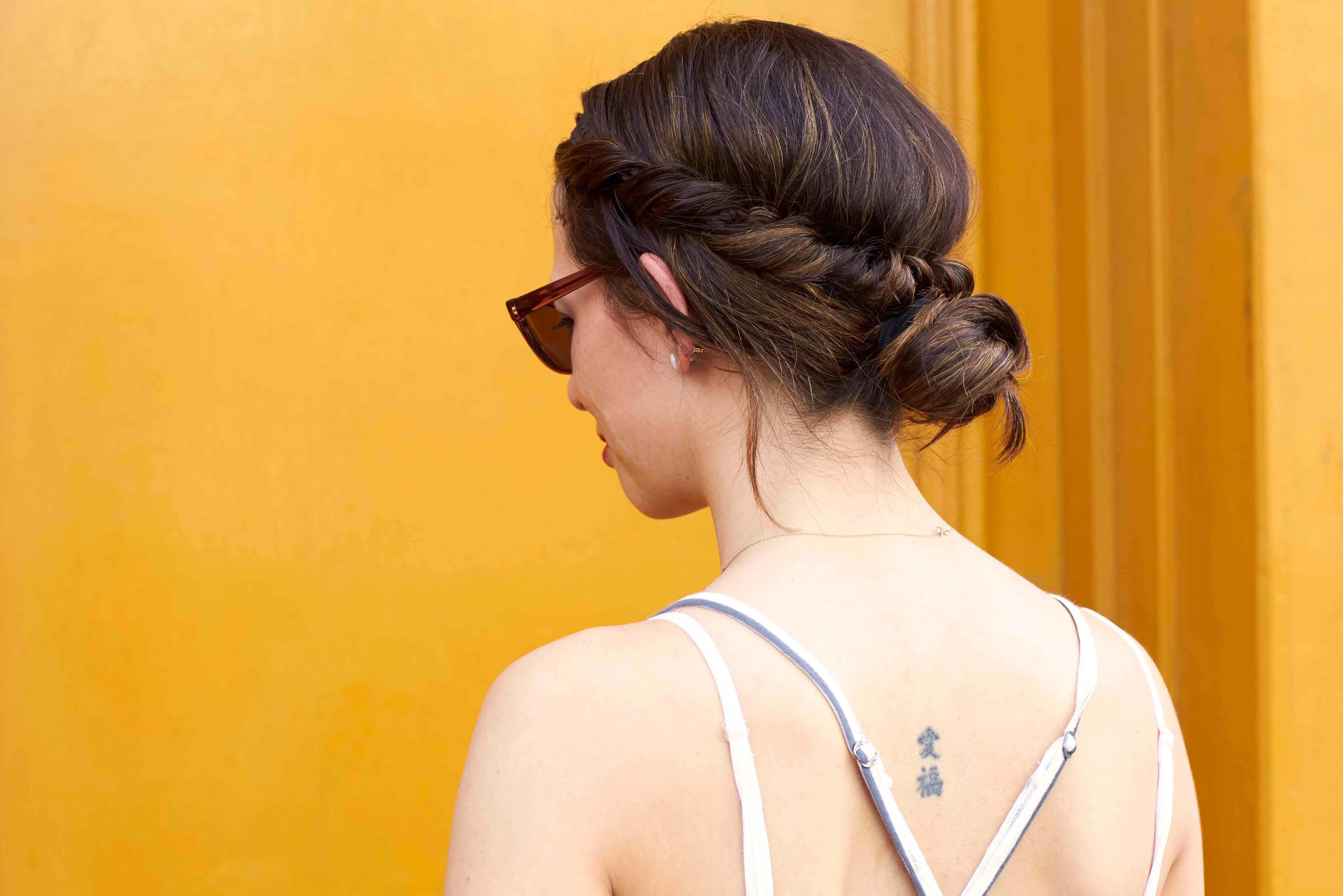 Best hairspray: Woman with brown hair in twisted low bun wearing a summer vest and sunglasses.