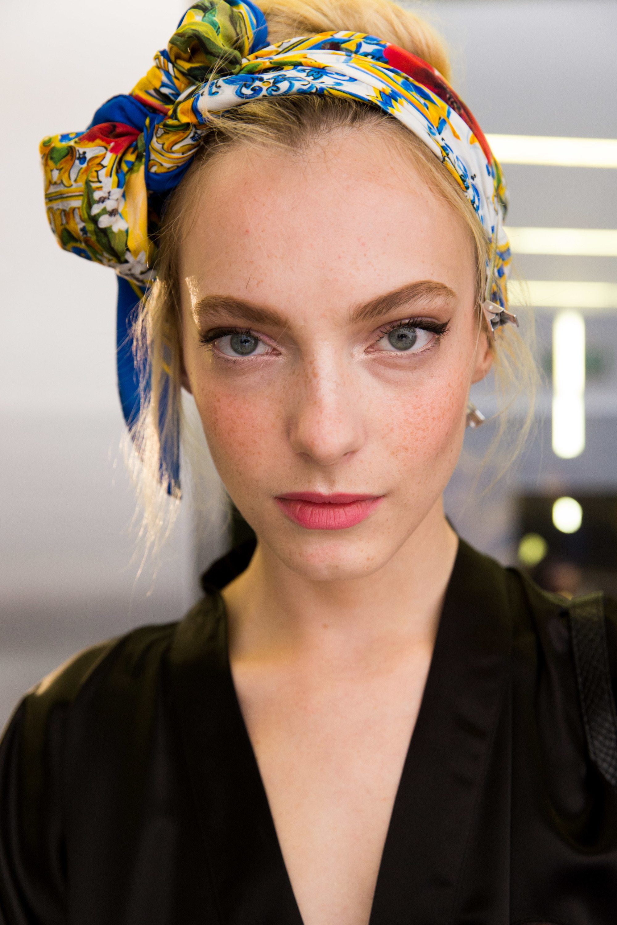 easy vintage hairstyles: backstage shot of model with a vintage messy updo with a printed scarf, wearing all black and posing