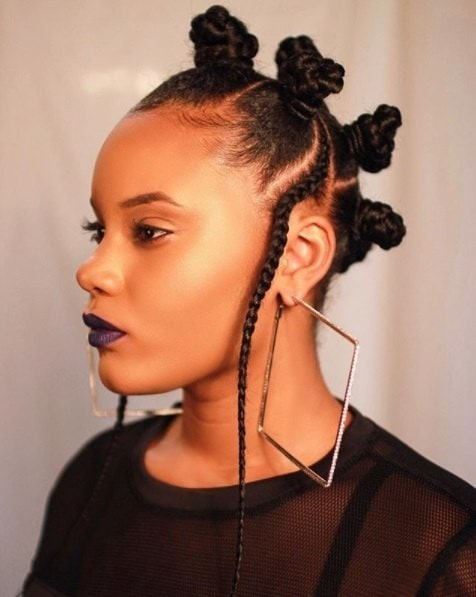 side profile of a lady with natural hair in bantu knots wearing oversized diamond shaped earrings