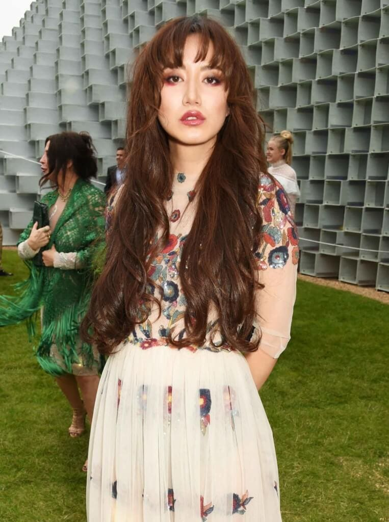 Betty Bachz at the serpentine summer party with her chocolate brown hair worn long and in waves, with blunt bangs