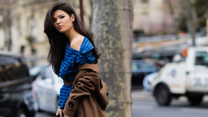 Long-haired brunette with blowout hair at Fashion week street style
