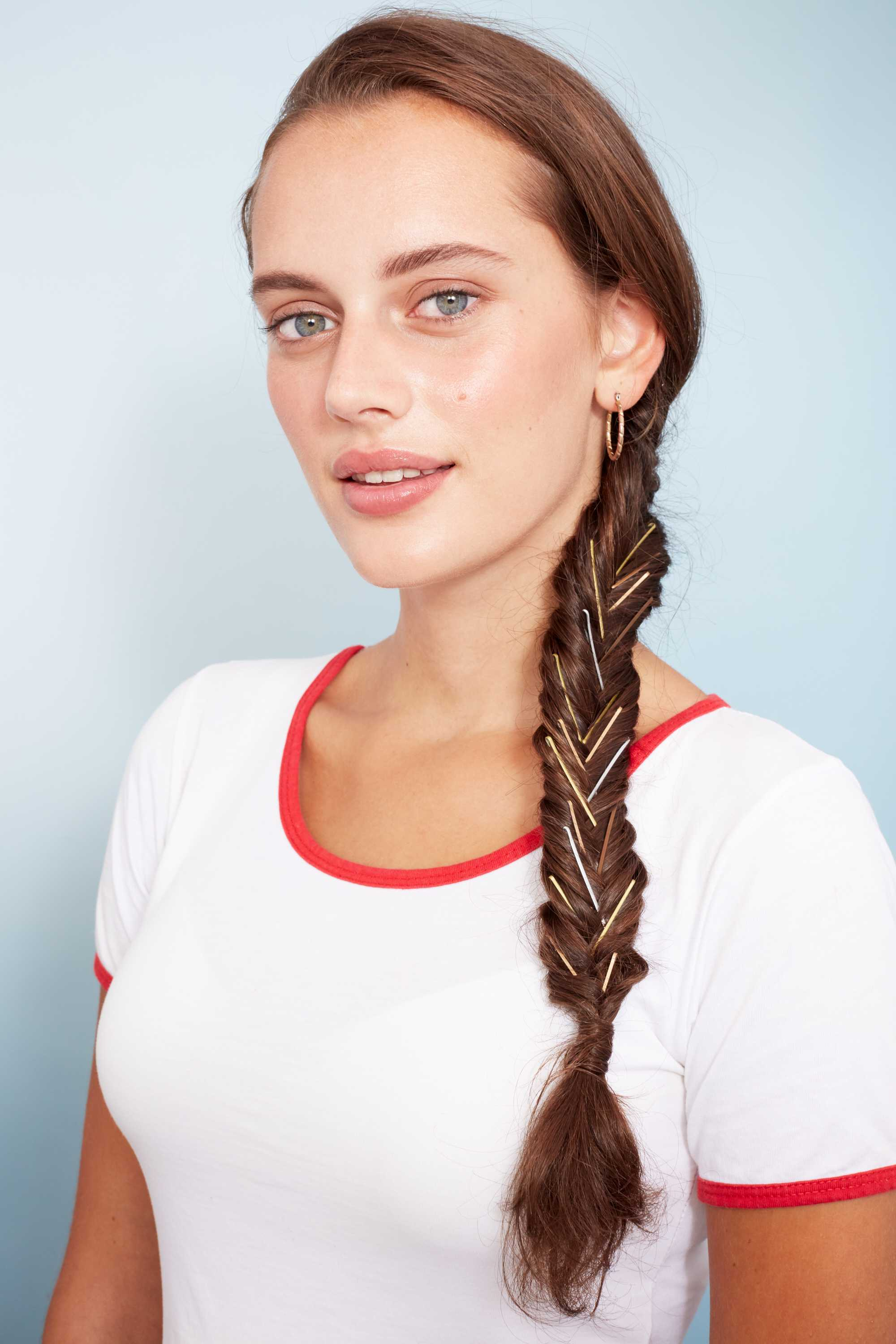 Bobby pin hairstyles: Close up shot of a woman with long chestnut brown hair styled into a side fishtail braid decorated with bobby pins, wearing white in a studio setting