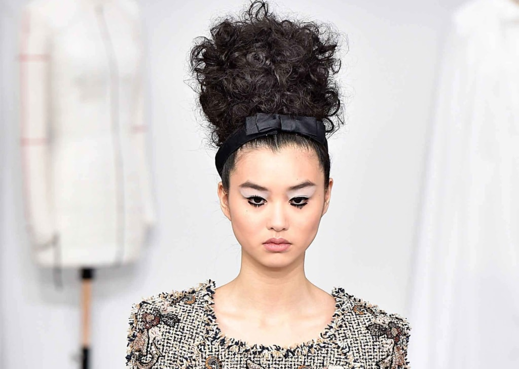 chanel couture aw16 runway model with big curly hair and a bow headband